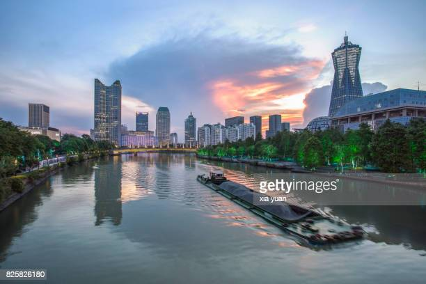 Ships sailing on the Grand Canal against Hangzhou Cityscape At Sunset,China