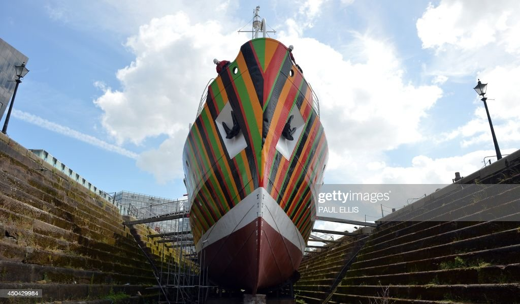 Shipworkers check the new paint work on the Edmund Gardner, a historic pilot ship placed in the dry dock at the Albert Dock in Liverpool, northwest England on June 11, 2014. The makeover was created by Venezuelan artist Carlos Cruz-Diez. The artist, known for his colourful large scale installations, has designed a contemporary version of a dazzle ship, a system for camouflaging ships introduced in early 1917, painting ships in vivid clashing angular patterns so their appearance was optically distorted making it almost impossible to determine their speed and direction. The exhibit is part of the Mersey International River Festival and is presented by Liverpool Biennial and Tate Liverpool. AFP PHOTO/PAUL ELLIS