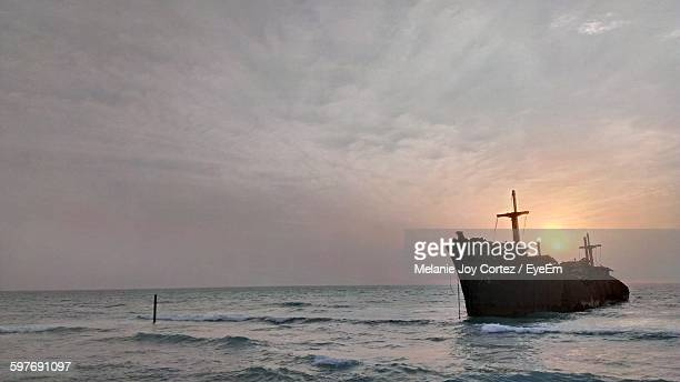 Shipwreck In Sea Against Sky During Sunset