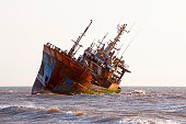 Abandoned broken ship-wreck beached on rocky ocean , western sahara coast