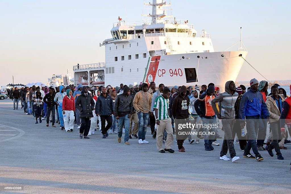 Shipwrecked migrants disembark from a rescue vessel as they arrive in the Italian port of Augusta in Sicily on April 16 2015 As many as 41 migrants...