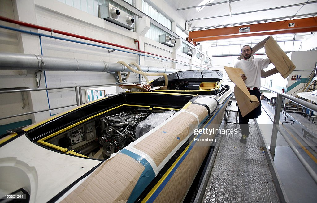 A shipwright carries wooden panels as he passes a Riva 'Aquariva Super' luxury yacht at the company's shipyard in Sarnico, Italy, on Tuesday, Oct. 2, 2012. Ferretti Group, whose Riva unit made boats for Brigitte Bardot and Sean Connery, intends to open an assembly plant in China as its new Chinese parent, Shandong Heavy, seeks to drive up sales in the world's most-populous country. Photographer: Alessia Pierdomenico/Bloomberg via Getty Images