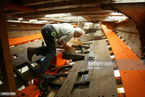 Shipwright Randy Purdue works below decks inside the Cho–Cho–San a 42 foot gaff rigged yawl being restored in a wooden boat repair facility run by...