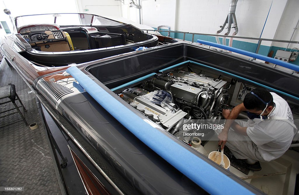 A shipwright works inside the engine bay of a Riva 'Aquariva Super' luxury yacht at the company's shipyard in Sarnico, Italy, on Tuesday, Oct. 2, 2012. Ferretti Group, whose Riva unit made boats for Brigitte Bardot and Sean Connery, intends to open an assembly plant in China as its new Chinese parent, Shandong Heavy, seeks to drive up sales in the world's most-populous country. Photographer: Alessia Pierdomenico/Bloomberg via Getty Images