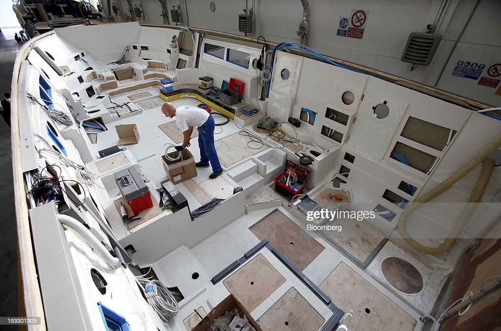 A shipwright works inside the hull of a Riva 'Virtus' luxury yacht at the company's shipyard in Sarnico, Italy, on Tuesday, Oct. 2, 2012. Ferretti Group, whose Riva unit made boats for Brigitte Bardot and Sean Connery, intends to open an assembly plant in China as its new Chinese parent, Shandong Heavy, seeks to drive up sales in the world's most-populous country. Photographer: Alessia Pierdomenico/Bloomberg via Getty Images
