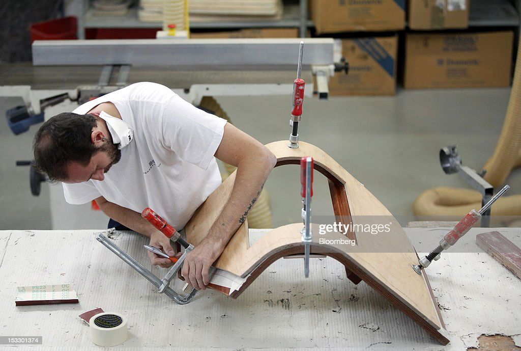 A shipwright works on a section of wood paneling for the interior of a luxury yacht inside the Riva boat building yard in Sarnico, Italy, on Tuesday, Oct. 2, 2012. Ferretti Group, whose Riva unit made boats for Brigitte Bardot and Sean Connery, intends to open an assembly plant in China as its new Chinese parent, Shandong Heavy, seeks to drive up sales in the world's most-populous country. Photographer: Alessia Pierdomenico/Bloomberg via Getty Images