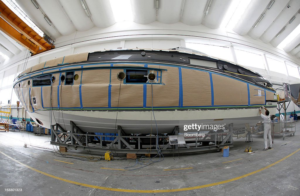 A shipwright works on the hull of a Riva 'Virtus' luxury yacht at the company's shipyard in Sarnico, Italy, on Tuesday, Oct. 2, 2012. Ferretti Group, whose Riva unit made boats for Brigitte Bardot and Sean Connery, intends to open an assembly plant in China as its new Chinese parent, Shandong Heavy, seeks to drive up sales in the world's most-populous country. Photographer: Alessia Pierdomenico/Bloomberg via Getty Images