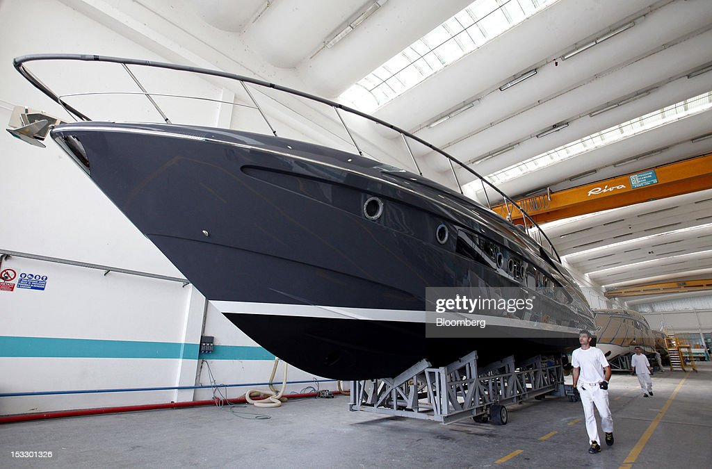 Shipwrights walk past Riva 'Virtus' luxury yachts inside company's shipyard in Sarnico, Italy, on Tuesday, Oct. 2, 2012. Ferretti Group, whose Riva unit made boats for Brigitte Bardot and Sean Connery, intends to open an assembly plant in China as its new Chinese parent, Shandong Heavy, seeks to drive up sales in the world's most-populous country. Photographer: Alessia Pierdomenico/Bloomberg via Getty Images