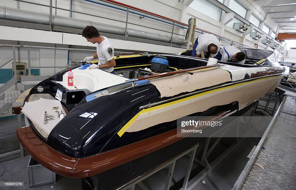 Shipwrights work inside a Riva 'Aquariva Super' luxury yacht at the company's shipyard in Sarnico, Italy, on Tuesday, Oct. 2, 2012. Ferretti Group, whose Riva unit made boats for Brigitte Bardot and Sean Connery, intends to open an assembly plant in China as its new Chinese parent, Shandong Heavy, seeks to drive up sales in the world's most-populous country. Photographer: Alessia Pierdomenico/Bloomberg via Getty Images