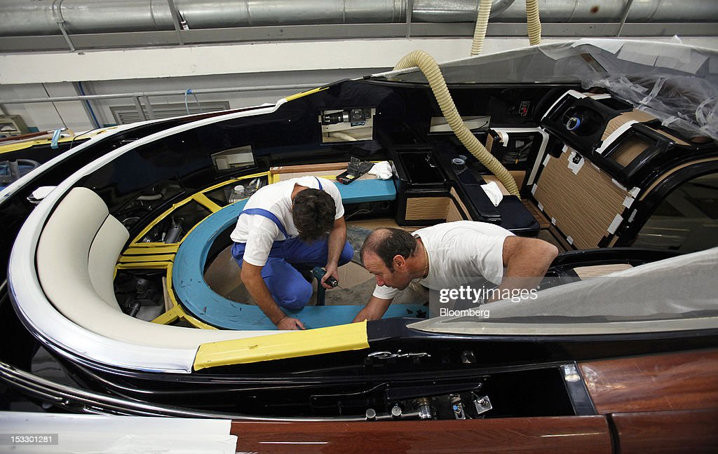 Shipwrights work inside the cabin of a Riva 'Aquariva Super' luxury yacht at the company's shipyard in Sarnico, Italy, on Tuesday, Oct. 2, 2012. Ferretti Group, whose Riva unit made boats for Brigitte Bardot and Sean Connery, intends to open an assembly plant in China as its new Chinese parent, Shandong Heavy, seeks to drive up sales in the world's most-populous country. Photographer: Alessia Pierdomenico/Bloomberg via Getty Images