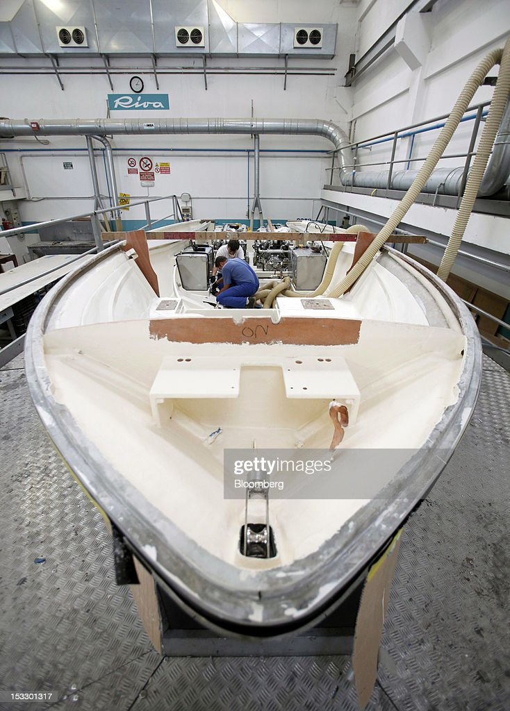 Shipwrights works inside the hull of a Riva 'Aquariva Super' luxury yacht at the company's shipyard in Sarnico, Italy, on Tuesday, Oct. 2, 2012. Ferretti Group, whose Riva unit made boats for Brigitte Bardot and Sean Connery, intends to open an assembly plant in China as its new Chinese parent, Shandong Heavy, seeks to drive up sales in the world's most-populous country. Photographer: Alessia Pierdomenico/Bloomberg via Getty Images