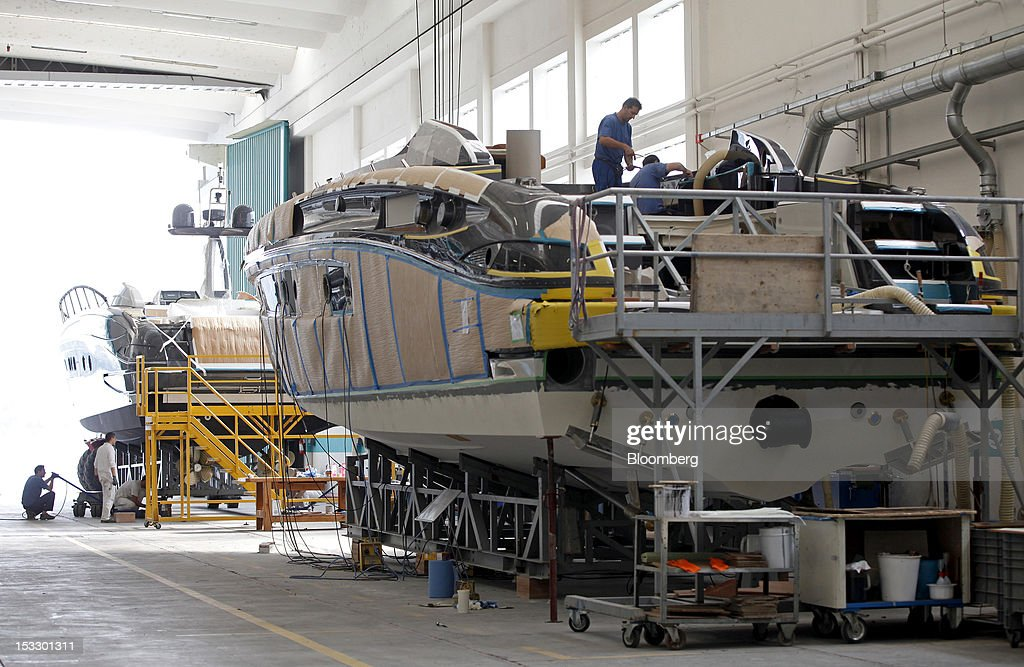 Shipwrights works on the deck of a Riva 'Virtus' luxury yacht at the company's shipyard in Sarnico, Italy, on Tuesday, Oct. 2, 2012. Ferretti Group, whose Riva unit made boats for Brigitte Bardot and Sean Connery, intends to open an assembly plant in China as its new Chinese parent, Shandong Heavy, seeks to drive up sales in the world's most-populous country. Photographer: Alessia Pierdomenico/Bloomberg via Getty Images