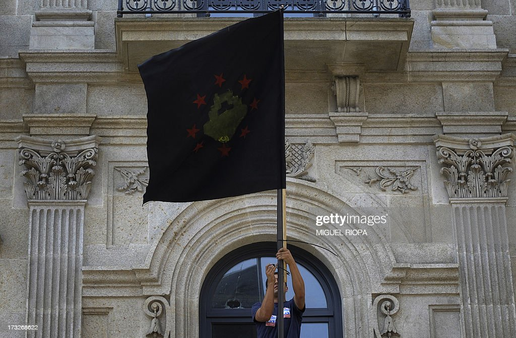 A shipyard worker dispalys a black flag on the building of the European Fisheries Control Agency during a protest against the repayment of state aids by Spanish shipbuilders in Vigo, on July 11, 2013. Brussels will decide by July 17 if the roughly three billion euros (4.0 billion USD) in state aid which Spanish shipbuilders received between 2005 and 2011 were unauthorised and if they will have to pay the money back. Unions have called for a day of protest and strikes on July 11 when European Union's commissioner for competition, Joaquin Almunia, will meet with representatives of Spanish shipbuilders in Brussels.
