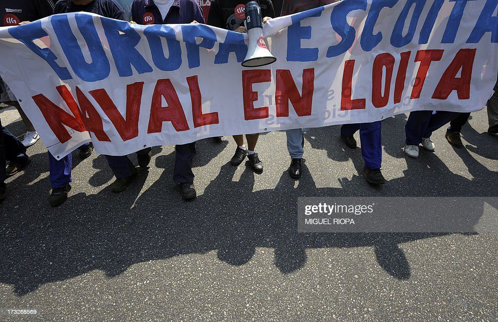 Shipyard workers hold a banner reading 'Listen Europa, shipyard struggles' as they demonstrate during a protest against the repayment of state aids by Spanish shipbuilders in Vigo, on July 11, 2013. Brussels will decide by July 17 if the roughly three billion euros (4.0 billion USD) in state aid which Spanish shipbuilders received between 2005 and 2011 were unauthorised and if they will have to pay the money back. Unions have called for a day of protest and strikes on July 11 when European Union's commissioner for competition, Joaquin Almunia, will meet with representatives of Spanish shipbuilders in Brussels.