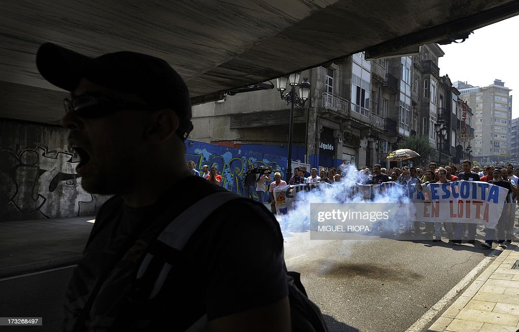 Shipyard workers use firecrackers as they take part in a protest against the repayment of state aids by Spanish shipbuilders in Vigo, on July 11, 2013. Brussels will decide by July 17 if the roughly three billion euros (4.0 billion USD) in state aid which Spanish shipbuilders received between 2005 and 2011 were unauthorised and if they will have to pay the money back. Unions have called for a day of protest and strikes on July 11 when European Union's commissioner for competition, Joaquin Almunia, will meet with representatives of Spanish shipbuilders in Brussels.