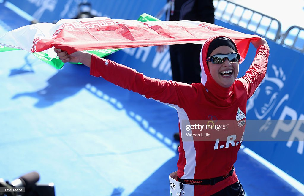 Shirin Gerami of Iran poses with her countes flag at the finish line for the Standard Distance Age-Group PruHealth ITU World Triathlon Grand Final London at Hyde Park on September 15, 2013 in London, England.