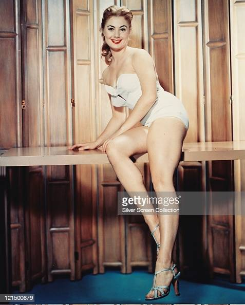 Shirley Jones US actress and singer wearing a white strapless swimsuit while posing on a wooden bench smiling in a studio portrait against a folding...