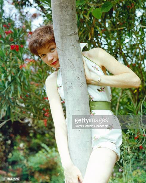 Shirley MacLaine US actress wearing a white floral print playsuit with a green belt posing behind a tree trunk circa 1955