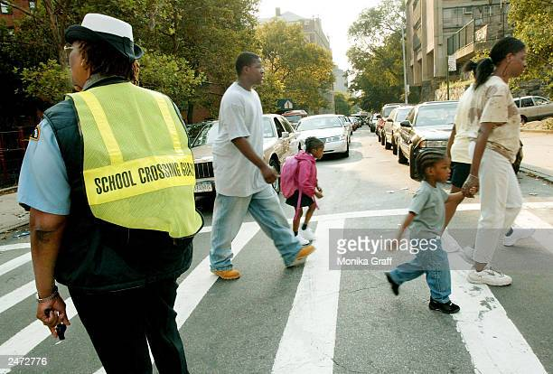 Shirley Miller who has been a crossing guard for 15 years helps parents and their children through an intersection on Amsterdam Avenue on the first...