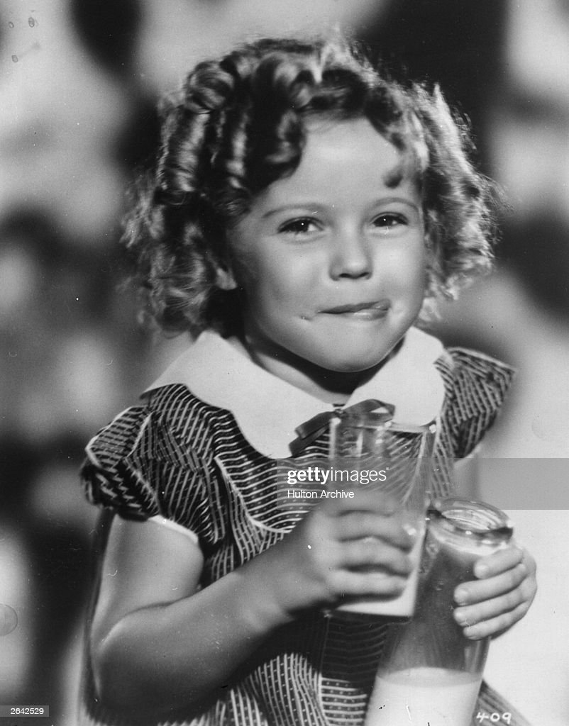 <a gi-track='captionPersonalityLinkClicked' href=/galleries/search?phrase=Shirley+Temple&family=editorial&specificpeople=69996 ng-click='$event.stopPropagation()'>Shirley Temple</a> (1928 - ) the American child star started performing in films at three years. She entered politics in the 60's and took on several ambassador positions representing her country. Pictured enjoying a soft drink with an impish grin on her face.