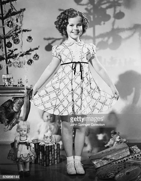 Shirley Temple wearing a dress made of printed spunrayon Fashioned along princess lines it has a swing skirt and belt with inserts of colored piping...