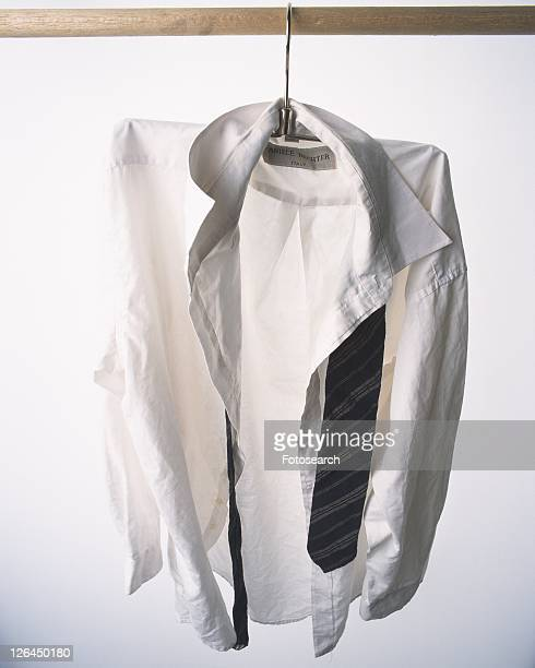 Shirt and tie hung at white wall