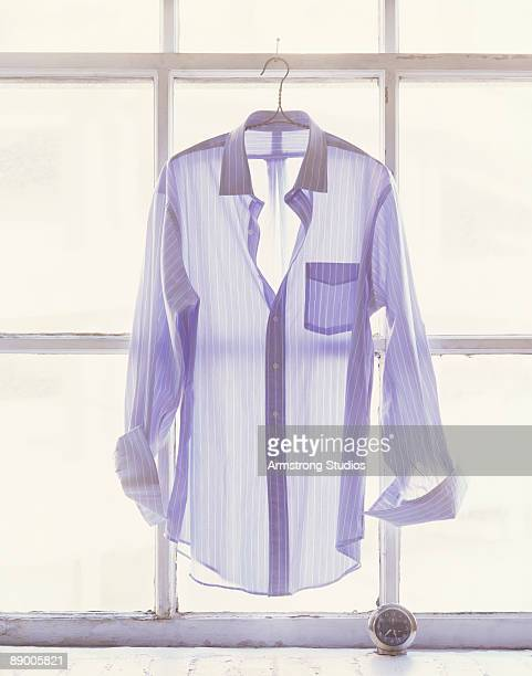 Shirt hanging in front of a window with a clock on sill