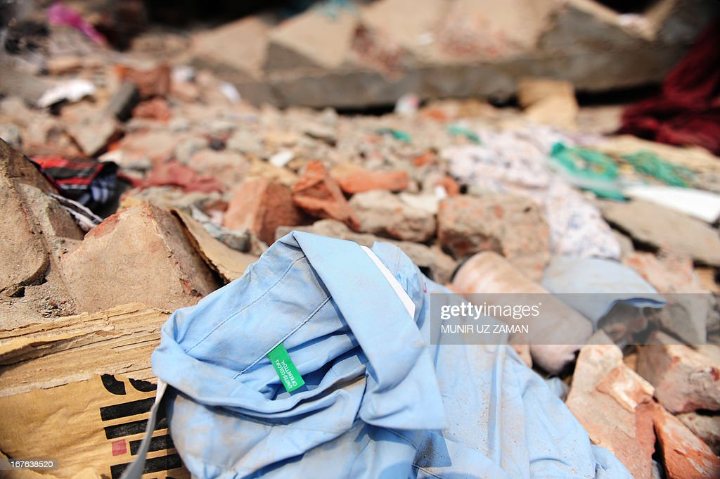 A shirt with a Benetton label lies in the rubble three days after a Bangladeshi garment eight-storey building collapsed in Savar, on the outskirts of Dhaka, on April 27, 2013. Police arrested two textile bosses over a Bangladeshi factory disaster as the death toll climbed to 332 and distraught relatives lashed out at rescuers trying to detect signs of life. AFP PHOTO/ Munir uz ZAMAN