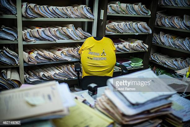 A shirt with a slogan reading 'Sin Justicia no hay derechos' is seen in a chair surrounded by lawsuits' files in the Criminal Court number 1 of...