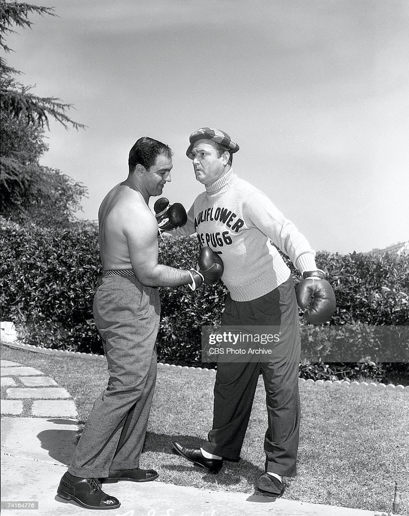 Shirtless American boxer Rocky Marciano (1923 - 1969) (left) (born Rocco Francis Marchegiano) mimes a gut punch to American comedian and entertainer Red Skelton (1913 - 1997), as the character 'Cauliflower McPugg,' in a promotional portrait for an episode of 'The Red Skelton Show,' September 24, 1956.