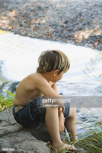 Shirtless boy sitting by creek