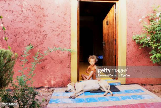 Shirtless Boy Sitting By Dog At Home