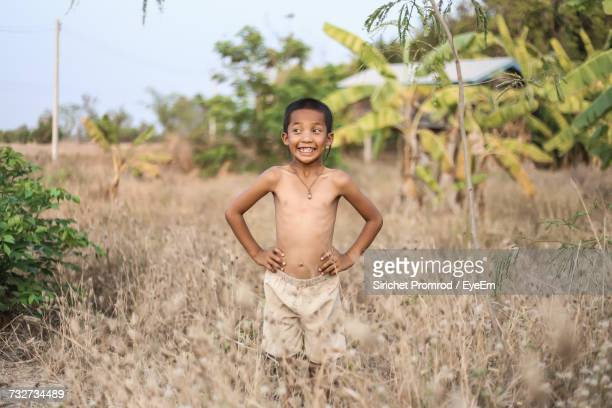 Shirtless Boy With Hands On Hip Standing Amidst Dead Plants At Farm