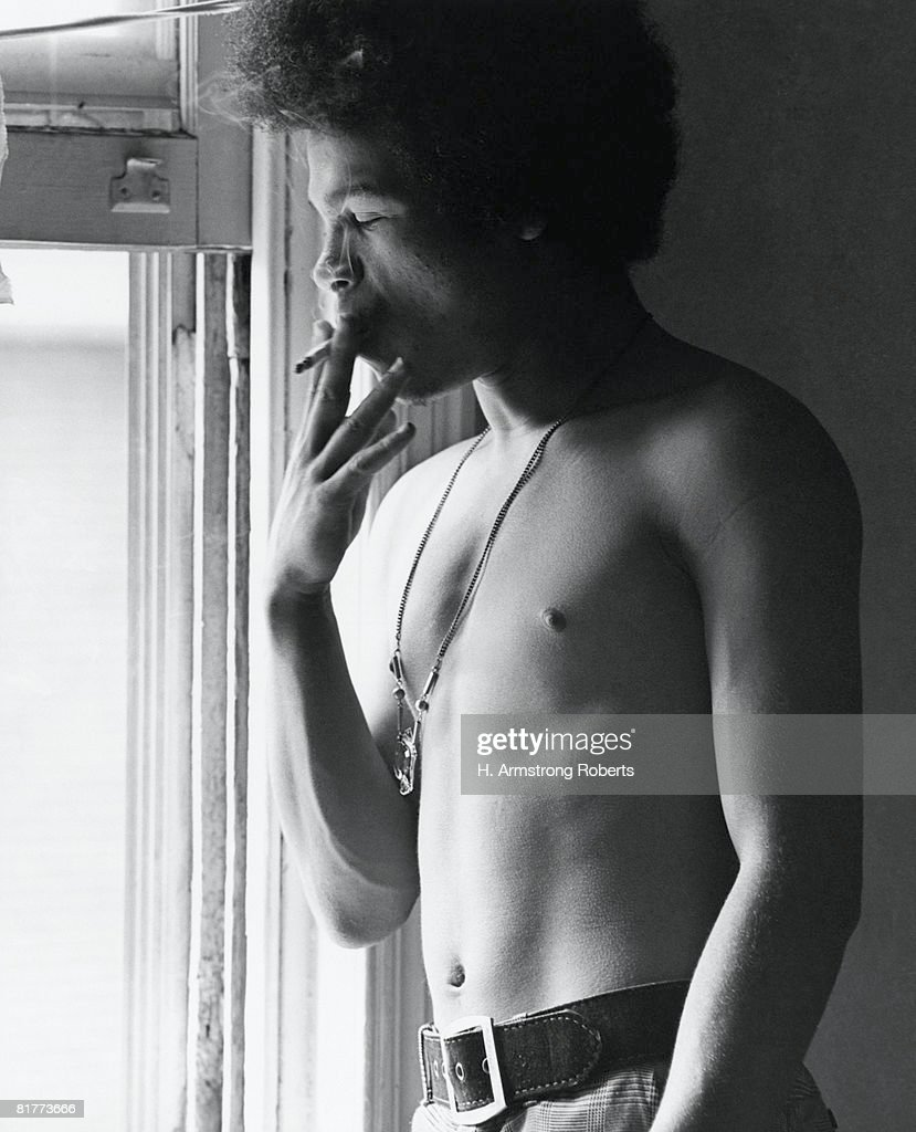 Shirtless Hispanic man with afro, standing by window, smoking. : Stock Photo