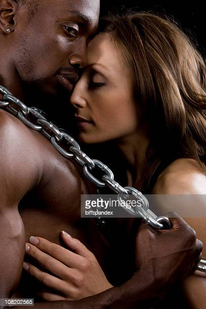 Shirtless Man and Woman Embracing While Caught in Chains