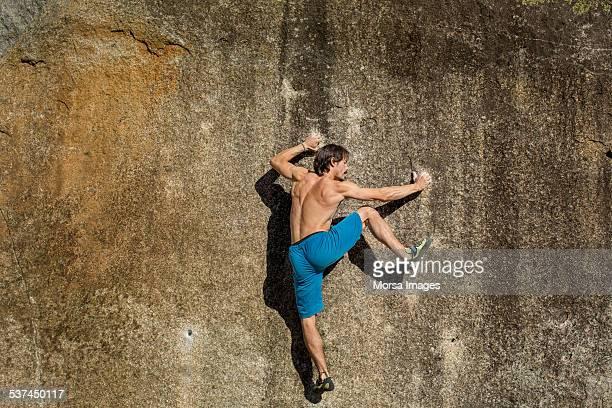 Shirtless man climbing on rock