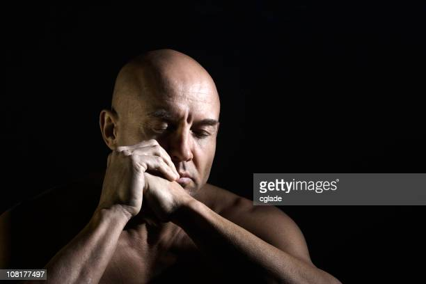 Shirtless Man Closing Eyes and Holding Hands Together
