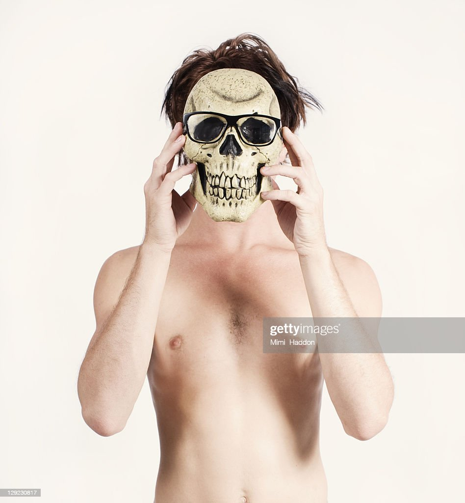 Shirtless Man Hiding Behind Skull with Glasses : Stock Photo