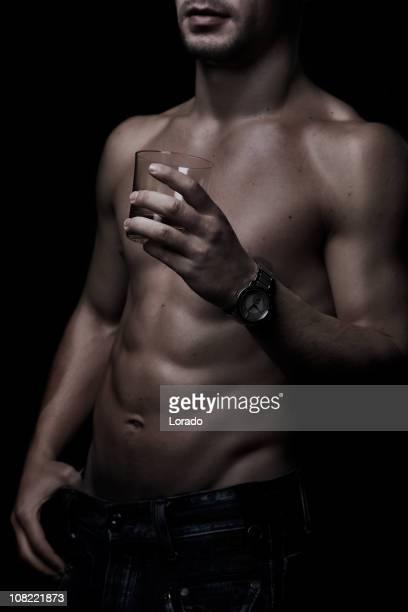 Shirtless Man Holding Glass of Whiskey