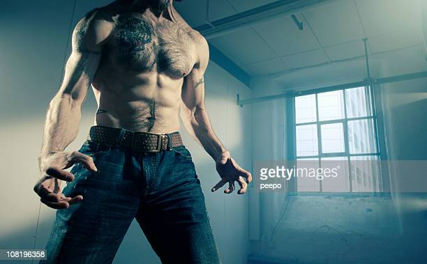 Shirtless Man in Empty Warehouse