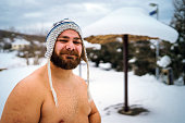 Outdoor portrait of shirtless man standing in a field covered with snow. He is wearing a hat and having fun, happy