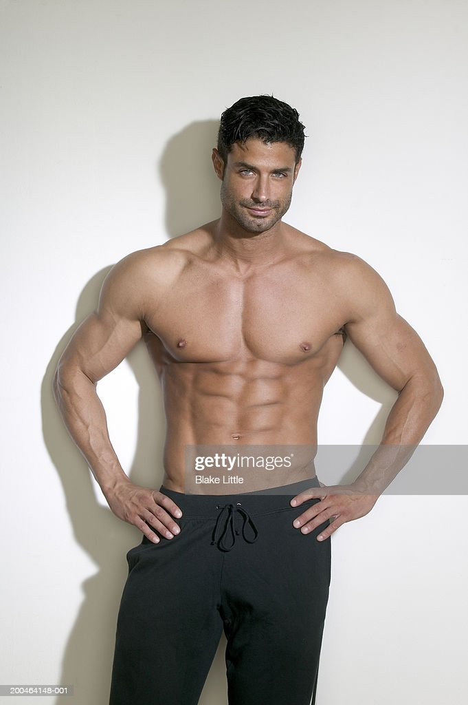 Shirtless man standing in front of white wall : Stock Photo