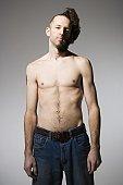 Shirtless man with half shaved hair and beard