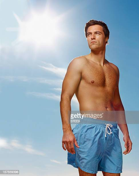 Shirtless young guy standing alone  against the blue sky
