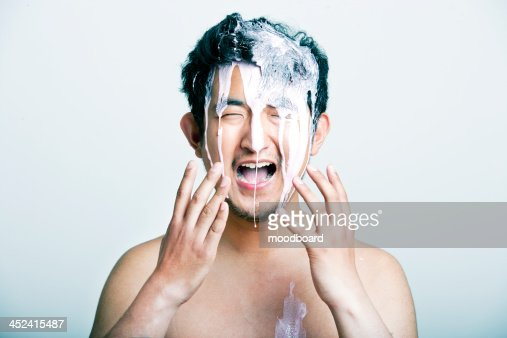 Shirtless young man with pink paint falling on his head against gray background : Stock-Foto