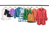 Colorful woman shirts and tops on clothes racks isolated over white