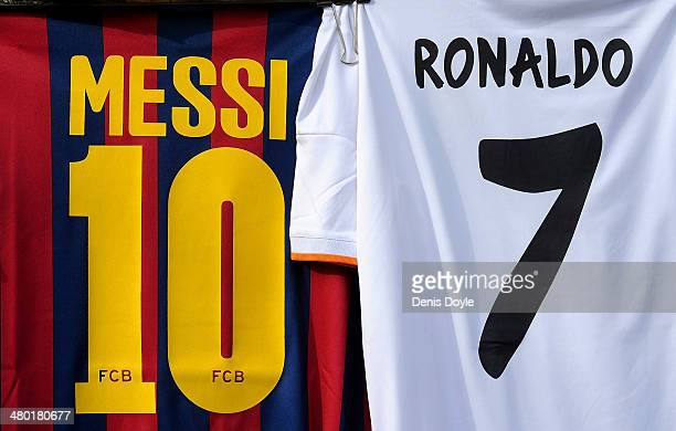 Shirts bearing the names of Lionel Messi of FC Barcelona and Cristiano Ronaldo of Real Madrid CF are seen on display at a merchandise stall prior to...