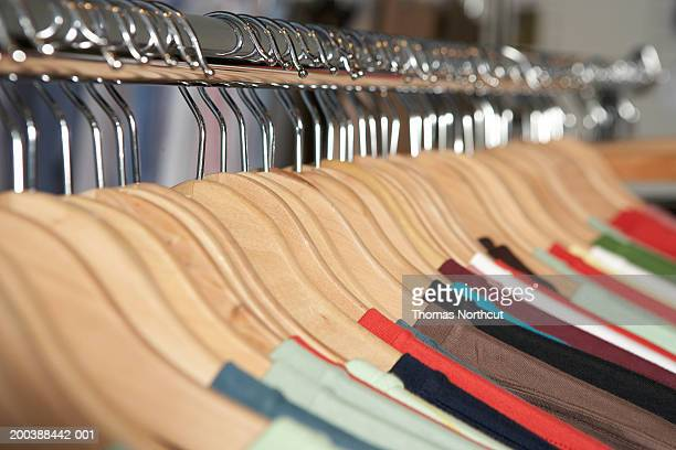 Shirts on wooden hangers on clothes rack (focus on hangers)