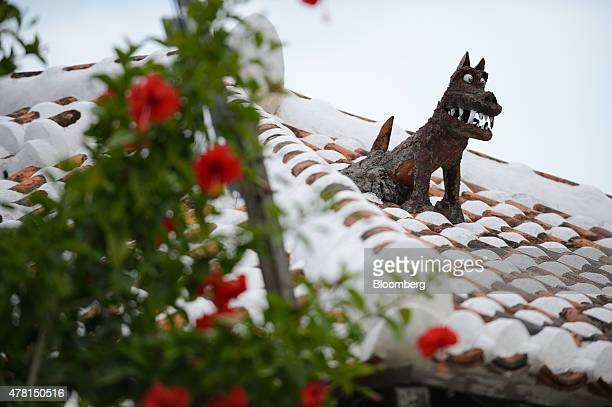 A Shisa lion sculpture sits on the roof of a house in Taketomi Okinawa Prefecture Japan on Saturday June 20 2015 The Abe administration aims to cap...