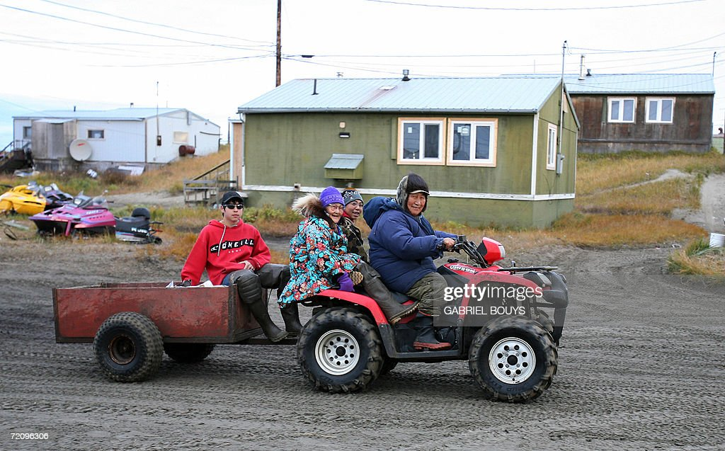 A family from Shishmaref, Alaska, returns home 26 September 2006. The village, home of Inupiat Eskimos, is located 20 miles (32kms) south of the Artic Circle. Shishmaref, on an island reachable only by air and inhabited for 4,000 years, is facing evacuation because of global warming. Temperatures that have risen 15F (4.4C) over the last 30 years are causing a reduction in sea ice, thawing of permafrost on which the village was built and making the shoreline vulnerable to erosion. Scientist report that other Alaskan towns are suffering similar problems, but point to Shismaref as an indicator of what can be expected in other parts of the world. Residents are planning to relocate to the mainland, making them the first refugees of global warming. AFP PHOTO/GABRIEL BOUYS =MORE PHOTOS IN IMAGE FORUM=